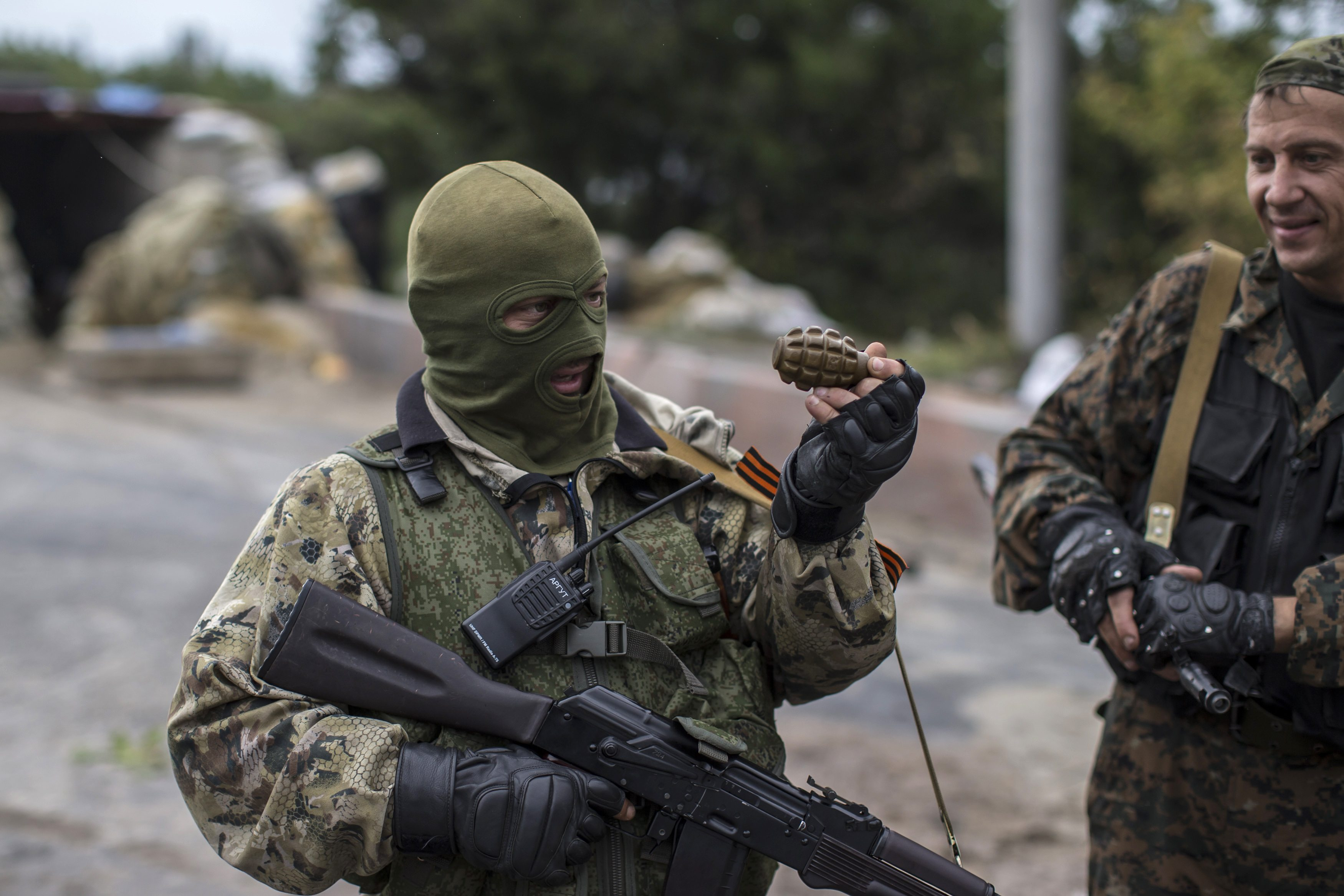 A Pro-Russian rebel holds a hand grenade at a checkpoint near the airport in Donets