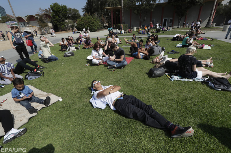 epa06155075 A man relaxes as he joined others of other spectators as a partial solar eclipse takes place outside the California Science Center in Los Angeles, California, USA, 21 August 2017. The 21 August 2017 total solar eclipse will last a maximum of 2 minutes 43 seconds and the thin path of totality will pass through portions of 14 US states, according to the National Aeronautics and Space Administration (NASA). EPA/MIKE NELSON