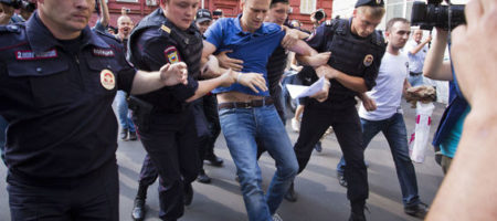 Police officers detain Russian opposition leader Alexei Navalny, center, outside the headquarters of Moscow's election commission in Moscow, Russia, Wednesday, July 10, 2013